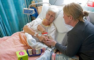 B8BTE8 Daughter visiting elderly mother patient in hospital bed Cheltenham UK. Image shot 02/2009. Exact date unknown.